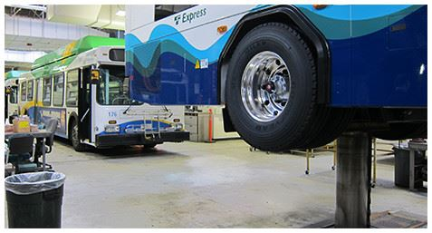 Two buses in an auto shop garage